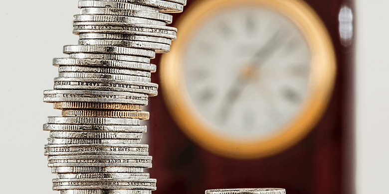 A stack of coins sitting in front of a blurred out clock.